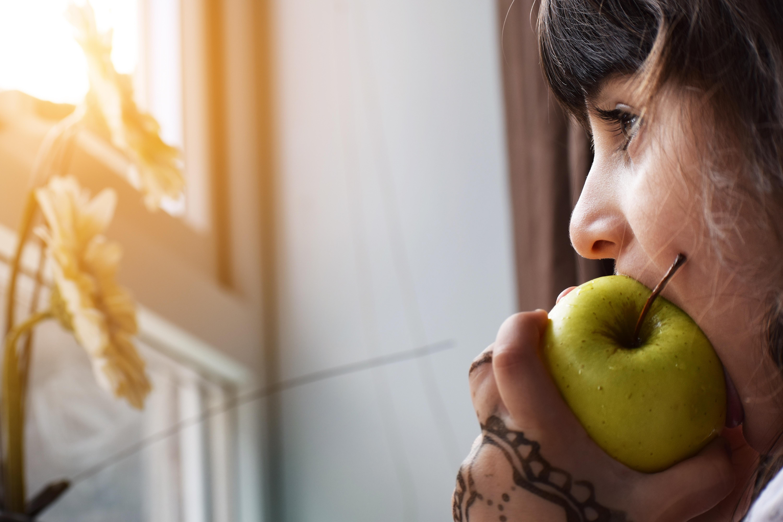 Pige tager en bid af et saftigt æble